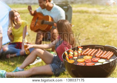 Young friends are waiting for roasted barbeque. They are sitting on grass in the nature and smiling. Man is playing guitar with pleasure. Focus on grill