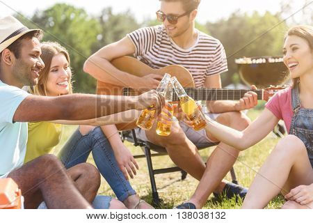 Young people having rest in nature together. They are drinking beer and smiling. Man is holding guitar and playing music