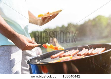Close up of young man cooking vegetables and meat on grill for his friends. He is standing outdoors and holding plate