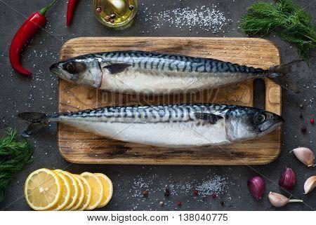 Fresh fish. Raw mackerel with salt lemon and spices on a dark background.