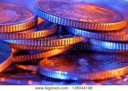 Heap of silver coins close up in colored lighting. Shallow depth of field