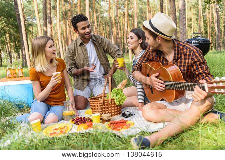 Joyful friends are making picnic in forest. They are talking and smiling. Women are drinking lemonade. Man is playing guitar