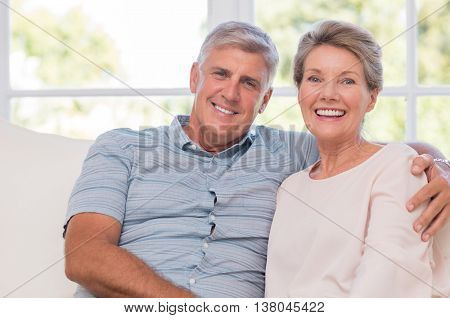 Smiling senior woman, and man sitting together on a sofa. Portrait of a candid older couple enjoying their retirement at home. Happy smiling senior couple embracing together and looking at camera. poster