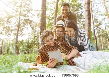 Cheerful friends are making picnic in nature. Man is lying on blanket and using tablet. Girls and guy are looking at technology with interest. They are smiling