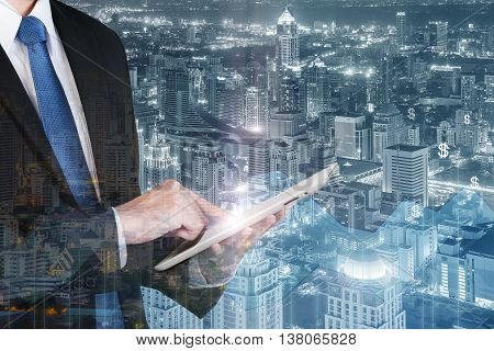 Business technology concept - Double exposure of business man using the tablet with financial business graph.