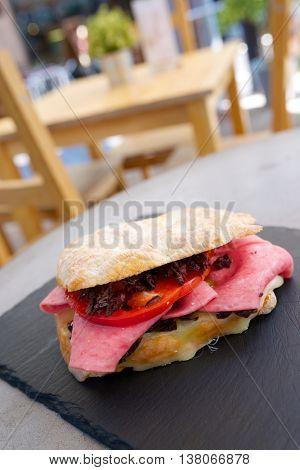 Mortadella sandwich, tomato and black olives.