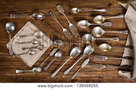Top view of collection of antique kitchen utensils ( spoon fork teaspoon knife tea-strainer) on a old wooden background.