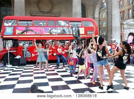 LONDON,UK - JULY 06, 2016:  Group of people dance in front of a London bus as part of a promotional campaign of a brand in Covent Garden, London.