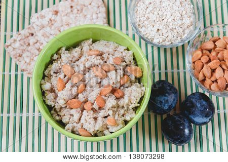 Porridge Oats with Nuts and Prunes on Wooden Table. Top View. Healthy Food Concept