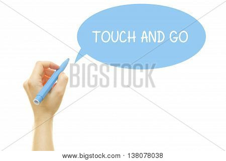 Woman hand writing TOUCH AND GO with a marker isolated on white.