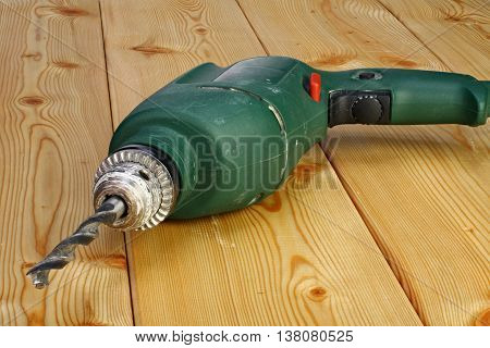 Electric drill on a wooden floor closeup