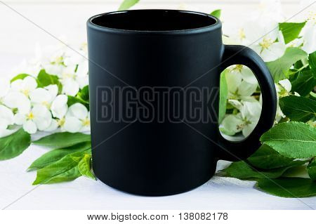 Black coffee mug mockup with apple blossom. Empty mug mockup for product presentation. Coffee cup mock-up for promotion brand or design.