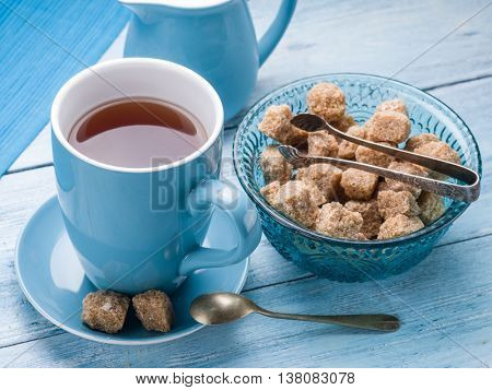 Cup of tea, milk jug and cane sugar cubes on old blue wooden table.