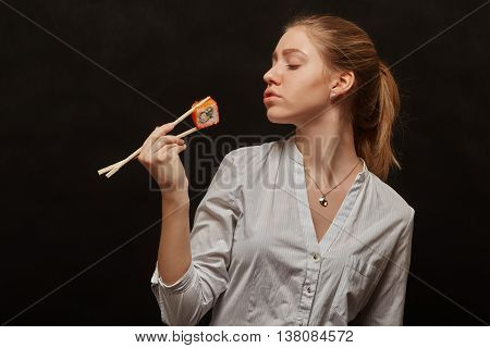 girl eating sushi roll on black background