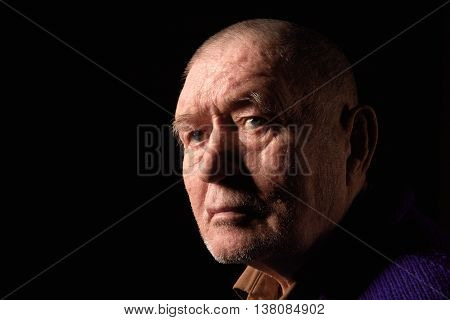 serious old man senior on black background