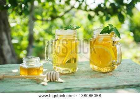 Iced tea with lemon slices and mint. A refreshing drink on a hot summer day in the garden. Shallow depth of field