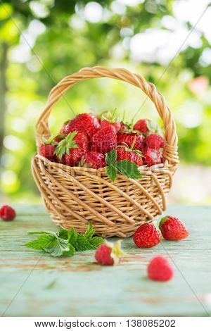 Ripe strawberries with leaves in a basket on wooden table on blurred background. Tasty and healthy berries.