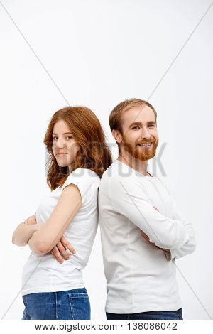 Cheerful redhead girl with boy dressed in white shirt  standing over white background.