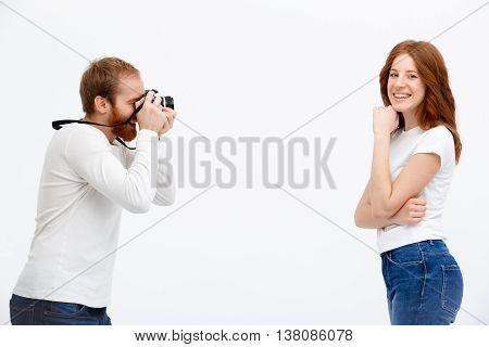 Cheerful redhead girl with photographer redhead boy  standing over white background.