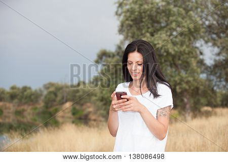 Relaxed brunette woman on the park looking at his mobile