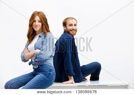 Beautiful redhead girl and boy posing over white background. Boy sitting at white table. Girl sitting on table.