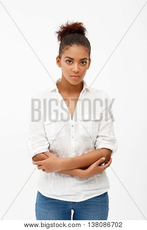 Portrait of young beautiful african girl looking at camera, arms crossed over white background.
