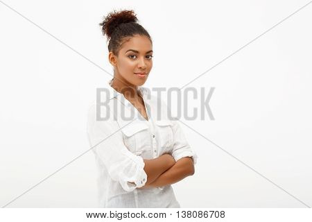Portrait of young beautiful african girl looking at camera, smiling, arms crossed over white background. Copy space.