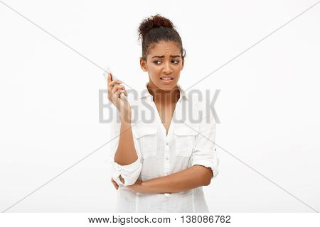Portrait of young beautiful african girl dipleased, looking at phone over white background.