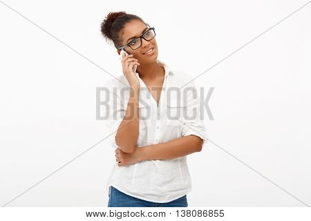 Portrait of young successful african business lady in glasses speaking on phone, smiling over white background. Copy space.