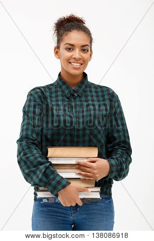 Portrait of young beautiful african girl in green blouse and jeans smiling, looking at camera with book over white background.