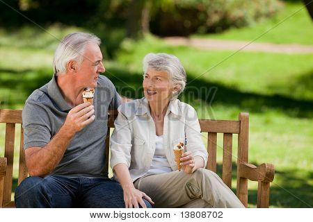 Senior Couple Eating An Ice Cream On A Bench