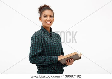 Portrait of young beautiful african girl in green blouse and jeans smiling with book over white background. Copy space.