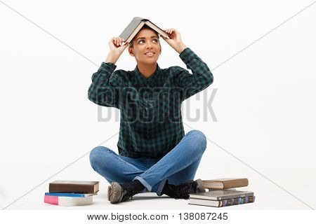 Portrait of young beautiful african girl in green blouse and jeans smiling, sitting on floor with books over white background. Copy space.