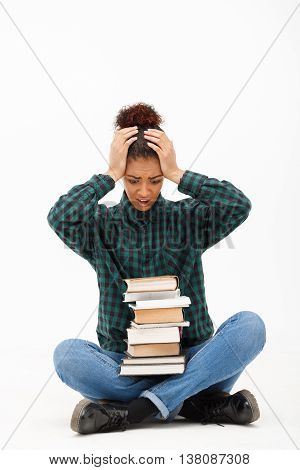 Portrait of upset young beautiful african girl in green blouse and jeans sitting on floor with books over white background. Copy space.