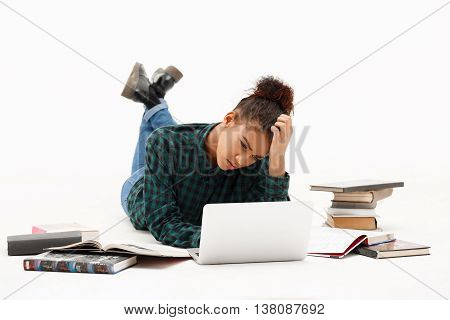 Portrait of upset young beautiful african girl with laptop and books thinking, looking at screen over white background.