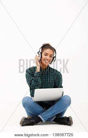 Portrait of young beautiful african girl in headphones with laptop listening music, smiling, looking at camera over white background. Copy space.