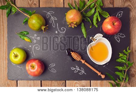 Jewish holiday Rosh Hashana background with apples pomegranate and honey on blackboard. View from above. Flat lay