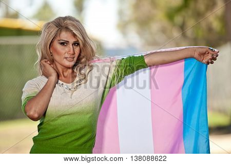 Transgender female with pride flag extended out on the left side of her body.