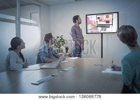 A laptop with graphic background against attentive business team following a presentation