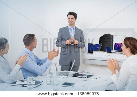 Smartphone, tablet computer and laptop against business team applauding their colleague