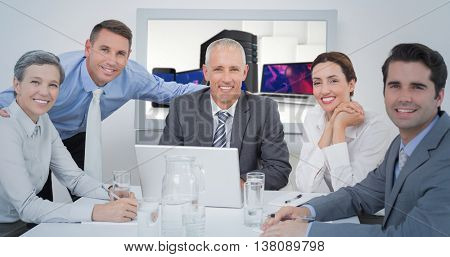 Business team looking at camera against smartphone, tablet computer and laptop