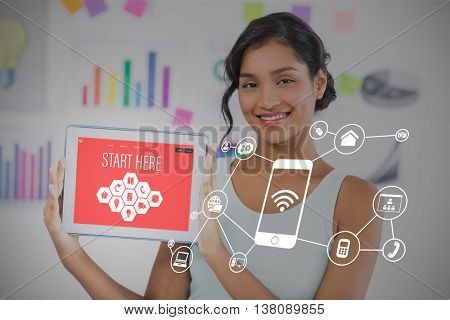 Happy businesswoman showing digital tablet in creative office against smartphone apps icons