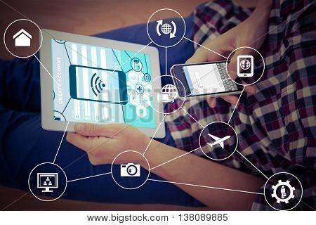 Smartphone apps icons against man using smartphone while holding digital tablet