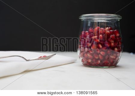 Front view of a glass container of pomegranate arils (seeds). A few seeds rest on a spoon on a napkin.