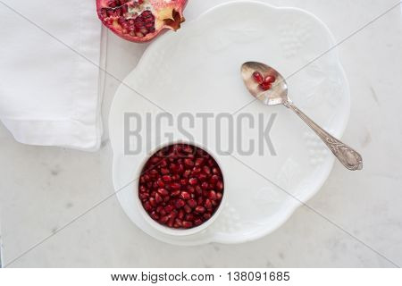 Top-down view of pomegranate seeds in a small bowl set on a dessert plate on white marble with napkin and silver sppon. Three arils (seeds) on spoon and half a pomegranate in background.