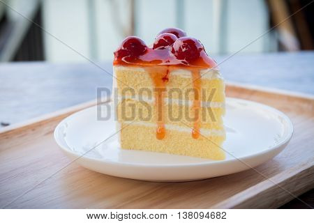 Sponge cherry cake with cherry syrup. Peace of cherry cake served in afternoon time. Cherry cake in cozy outdoor cafe.