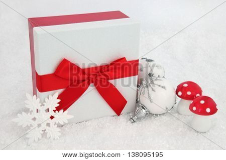 Christmas glitter gift box with red bow, white snowflake baubles and fly agaric decorations on snow background.