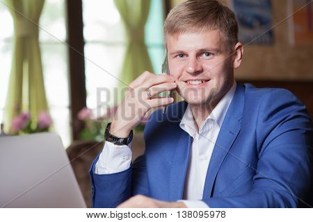 Happy Smiling Businessman Wearing A Blue Suit And Using Modern Smartphone In Office At Early Morning
