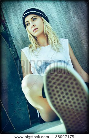 Pretty blond skater girl sitting