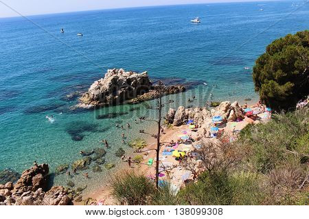 Sant Pol de Mar, Spain - July 9, 2016: People enjoying summer on a beach with transparent waters near the town of Sant Pol de Mar in Costa Brava